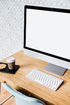 Nahaufnahme des computers und der tastatur auf hölzernem schreibtisch