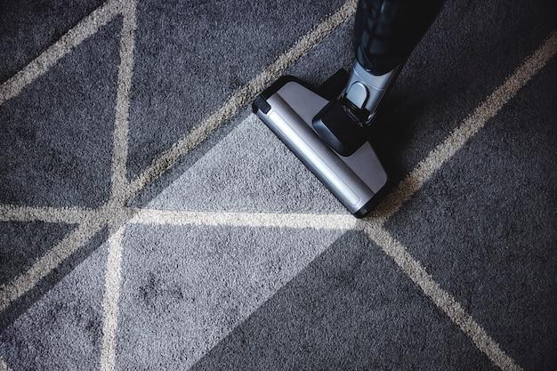 Nahaufnahme des dampfreinigers, der sehr schmutzigen teppich reinigt.