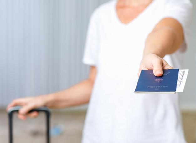 Nahaufnahme des deutschen passes und des coronavirus covid-19 impfausweises in weiblicher hand in unscharfem hintergrund, die nach der sperrung trolley-gepäcktasche ziehen, die ins ausland reist