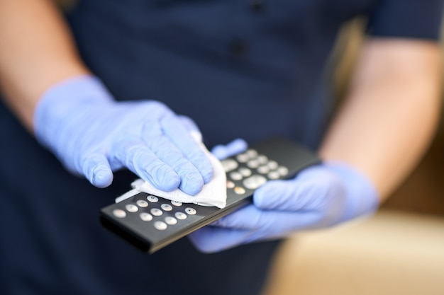 Nahaufnahme des dienstmädchens mit schutzhandschuhen beim reinigen der konsole im hotelzimmer. hotelservicekonzept