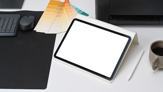 Nahaufnahme des digitalen tablets mit weißem bildschirm auf dem grafikdesigner-arbeitsbereich.