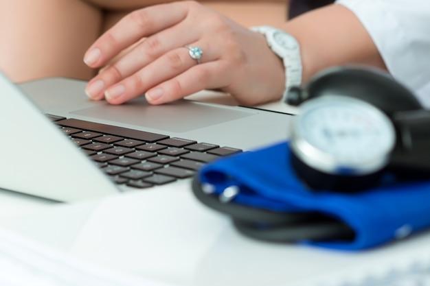 Nahaufnahme des doktorarbeitstisches. ärztin arbeitet am laptop. krankenhausarbeitsbereich. konzept für gesundheitswesen, medizinische versorgung, behandlung, hypotonie oder bluthochdruck