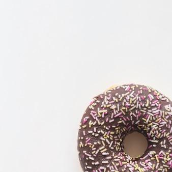 Nahaufnahme des donuts mit besprüht auf weißem hintergrund