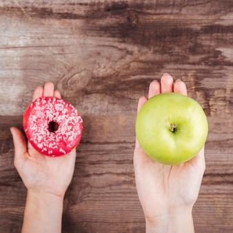 Nahaufnahme des donuts und des apfels in den palmen