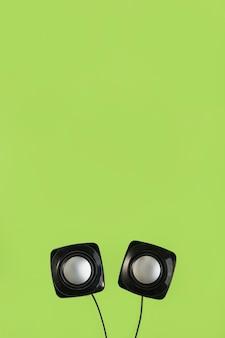 Nahaufnahme des drahtlosen lautsprechers auf grünem hintergrund