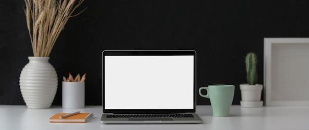 Nahaufnahme des dunklen modernen arbeitsbereichs mit laptop, zubehör und dekorationen