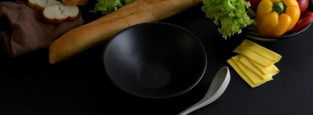Nahaufnahme des dunklen modernen konzeptküchentischs mit küchengeschirr, französischem baguette und zutaten