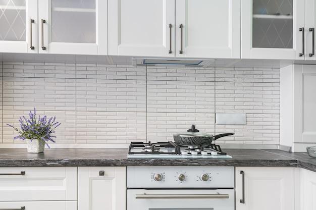 Nahaufnahme des einfachen gut gestalteten modernen weißen kücheninnenraums, niedrige vorderansicht
