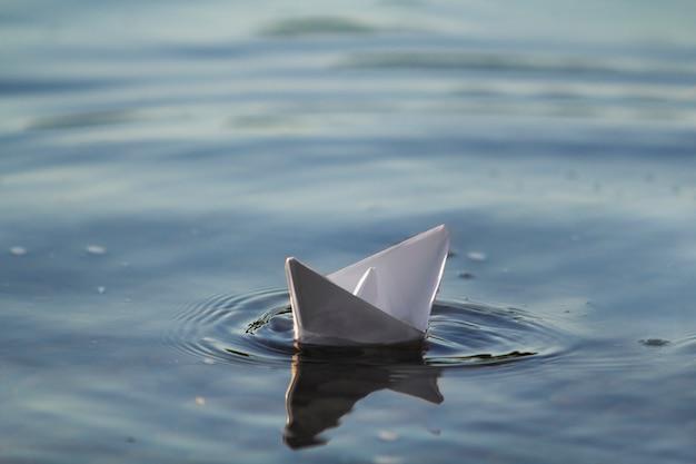Nahaufnahme des einfachen kleinen weißen origami-papierboots, das ruhig im blauen klaren fluss oder im meerwasser unter hellem sommerhimmel schwimmt. freiheit, träume und fantasien konzept, copyspace hintergrund.