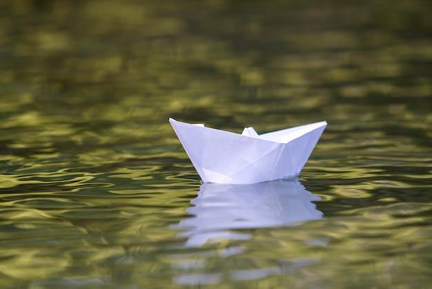 Nahaufnahme des einfachen kleinen weißen origamipapierbootes, das ruhig in gelben klaren fluss schwimmt