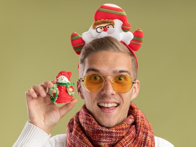 Nahaufnahme des eingeprägten jungen gutaussehenden kerls, der weihnachtsmann-stirnband und schal trägt, die kamera betrachten schneemann-weihnachtsverzierung lokalisiert auf olivgrünem hintergrund betrachten
