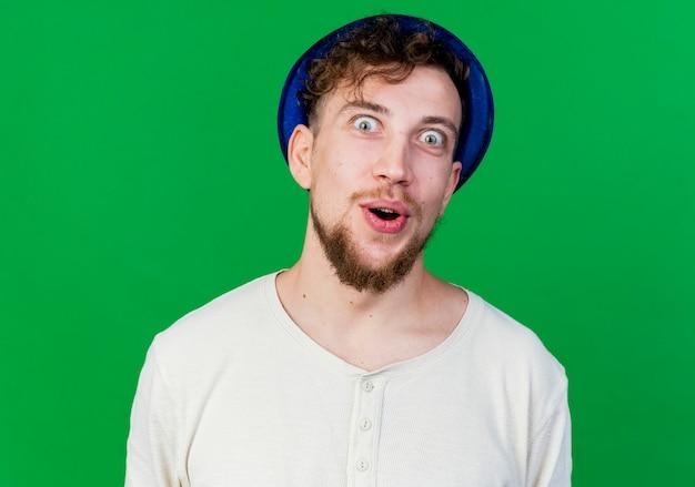 Nahaufnahme des eingeprägten jungen gutaussehenden slawischen partei-kerls, der partyhut trägt und kamera lokalisiert auf grünem hintergrund trägt