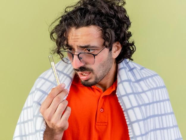 Nahaufnahme des eingeprägten jungen kaukasischen kranken mannes, der gläser trägt, die im karierten halten eingewickelt sind und thermometer betrachten, das auf olivgrüner wand isoliert wird