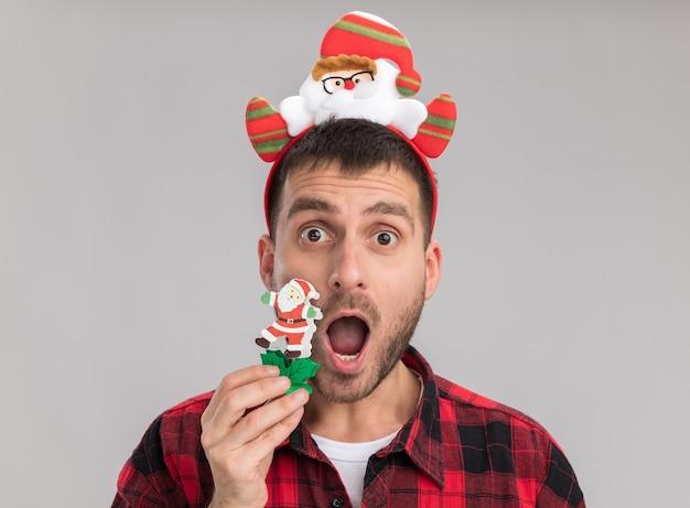 Nahaufnahme des eingeprägten jungen kaukasischen mannes, der das weihnachtsstirnband berührt, das gesicht mit schneemannspielzeug berührt, das kamera lokalisiert auf weißem hintergrund betrachtet