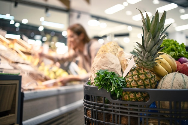 Nahaufnahme des einkaufswagens am supermarkt voll von lebensmitteln, obst und gemüse, während im hintergrund frau produkt aus den regalen nimmt