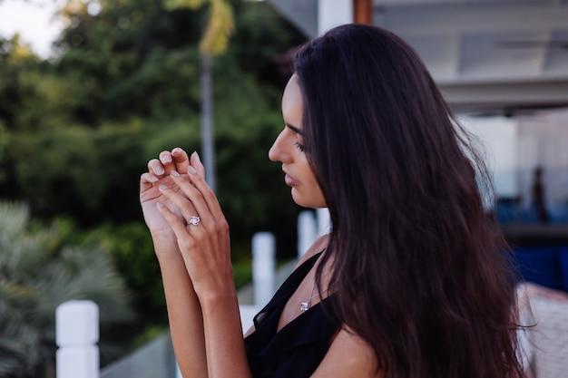Nahaufnahme des eleganten diamantrings am frauenfinger. frau, die schwarzes kleid trägt. liebes- und hochzeitskonzept. weiches natürliches tageslicht und selektiver fokus.