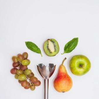 Nahaufnahme des elektrischen handmixers mit trauben; birnen; apfel; halbierte kiwi und basilikum auf weißem hintergrund