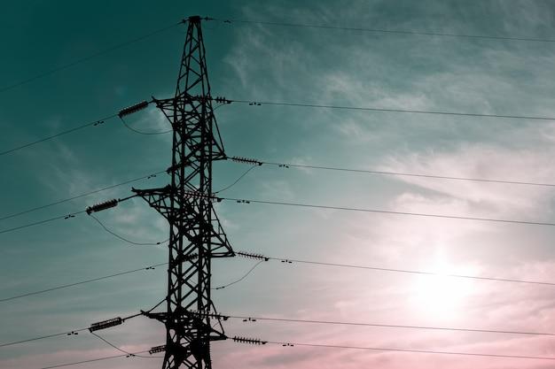Nahaufnahme des elektrischen hochspannungsmastes des metalls auf hintergrund des sonnenaufgangshimmels.