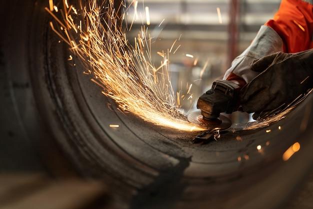 Nahaufnahme des elektrischen radschleifens bei industriearbeitern, die metallrohre mit vielen scharfen funken schneiden
