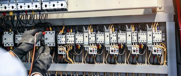 Nahaufnahme des elektrotechnikers unter verwendung von messgeräten zur überprüfung der elektrischen stromspannung am leistungsschalter.