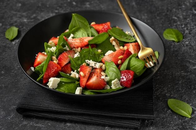 Nahaufnahme des erfrischenden frühlingssalats mit erdbeeren, spinat, feta und nüssen