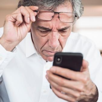 Nahaufnahme des ernsten älteren Mannes, der intelligentes Telefon betrachtet