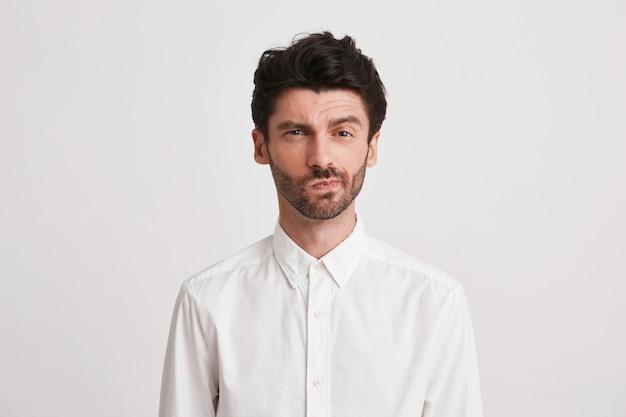 Nahaufnahme des ernsthaften unzufriedenen jungen geschäftsmannes mit borsten trägt hemd sieht nachdenklich und unzufrieden isoliert auf weiß aus