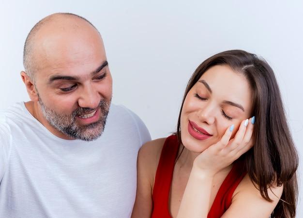 Nahaufnahme des erwachsenen erfreuten paares mann, der frau und frau betrachtet, die hand auf gesicht mit geschlossenen augen setzen