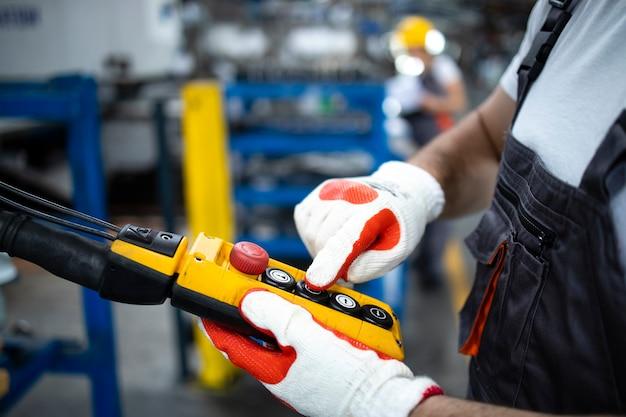 Nahaufnahme des fabrikarbeiters, der industriemaschine mit druckknopf-joystick in der produktionshalle betreibt