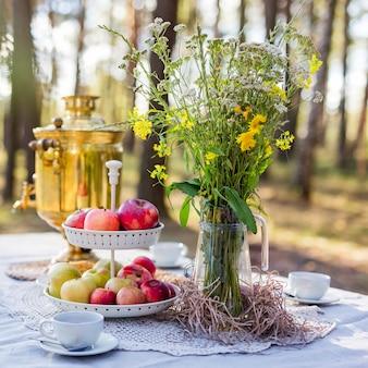 Nahaufnahme des feldblumenstraußes in einer vase mit frischen äpfeln, einigen snacks, russischem samowar, teetassen auf tisch im freien. bild zuschneiden