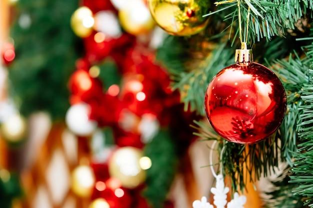 Nahaufnahme des festlich geschmückten weihnachtsbaums im freien mit leuchtend roten kugeln auf unscharfem hintergrund.