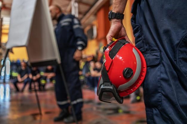 Nahaufnahme des feuerwehrmanns, der einen helm hält und seinem chef zuhört, der zeichnet und über unfall spricht.