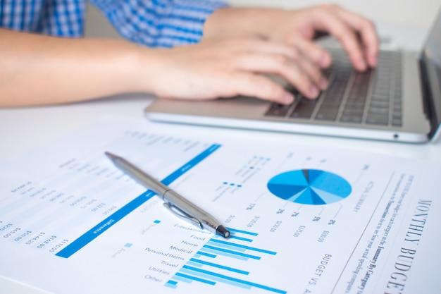 Nahaufnahme des finanzdiagramms einer geschäftsarbeitskraft, die an laptop arbeitet