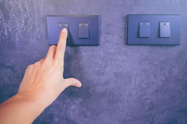 Nahaufnahme des fingers am lichtschalter an der wand ausschalten energiesparkonzept