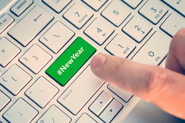 Nahaufnahme des fingers auf der tastaturtaste mit dem wort neujahr. ein männlicher finger drückt einen farbknopf auf einer grau-silbernen tastatur eines modernen laptops. schaltfläche mit aufschrift hautnah.