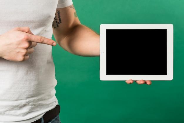 Nahaufnahme des fingers des mannes den finger in richtung zur digitalen tablette mit schwarzer bildschirmanzeige zeigend