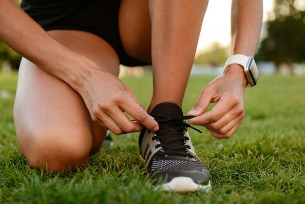 Nahaufnahme des fitnessmädchens, das ihre schnürsenkel bindet