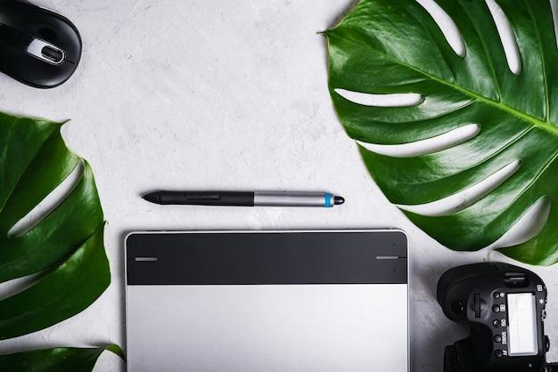 Nahaufnahme des fotografen des arbeitsplatzes des grafikdesigners. tablet, stift, kamera, optische funkmaus, grünes blatt von monstera.
