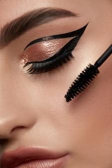 Nahaufnahme des frauenauges mit goldenem luxus-make-up und mascara bru