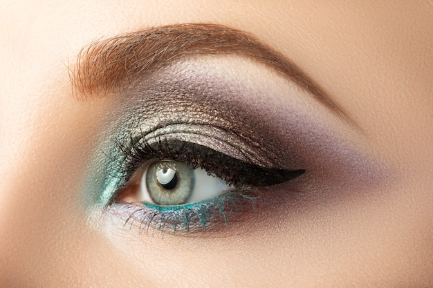 Nahaufnahme des frauenauges mit kreativem modernem make-up. rauchige augen und pfeil.