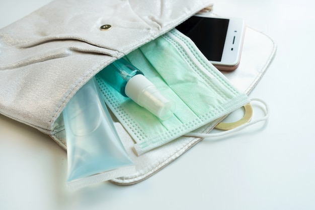 Nahaufnahme des frauenbeutels mit smartphone, desinfektionsmittel, alkoholspray und schützender gesichtsmaske. gesundheitskonzept.