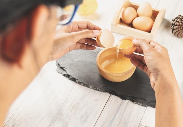 Nahaufnahme des frauenchefs ein ei in die hölzerne schüssel brechend. kochen konzept.