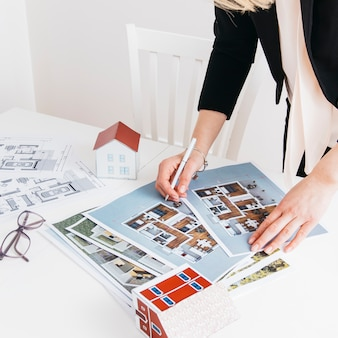 Nahaufnahme des frauenhandbehälters arbeitend an plan im büro Premium Fotos