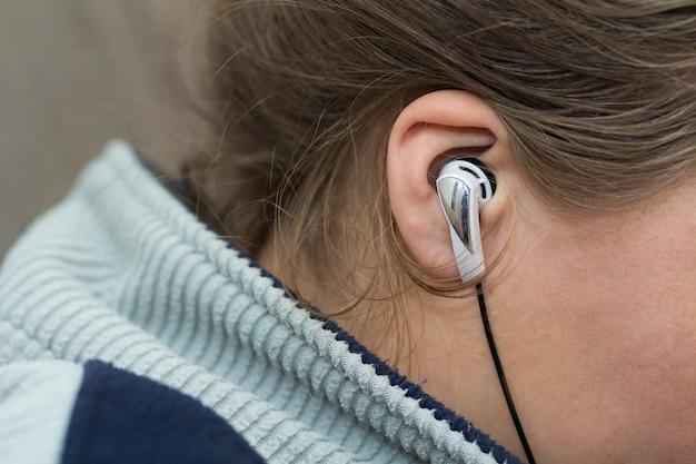Nahaufnahme des frauenohrs mit weißem earbud listenin musik