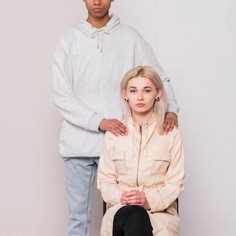 Nahaufnahme des freundes stehend mit seiner blonden jungen frau, die auf stuhl gegen weißen hintergrund sitzt