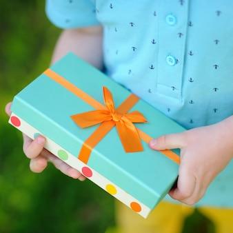 Nahaufnahme des freundlich eingewickelten geburtstagsgeschenks, das von einem kind gehalten wird