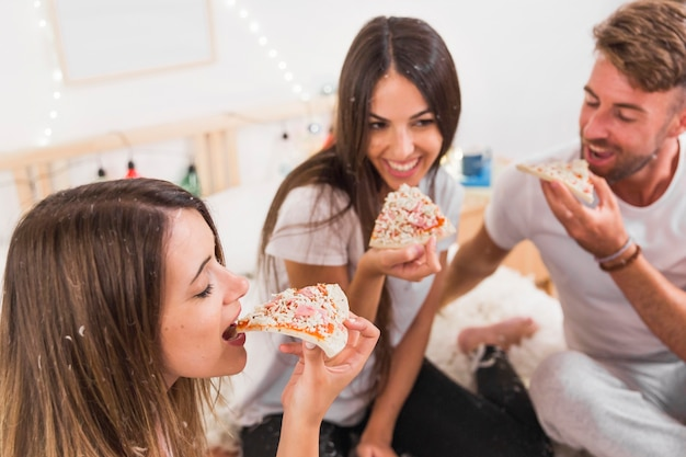 Nahaufnahme des freunds pizza vor paaren essend
