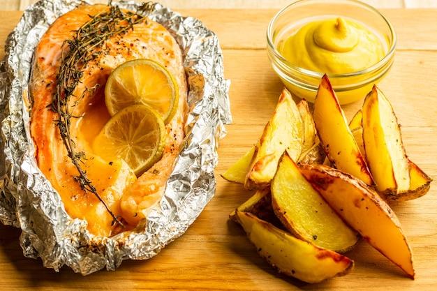 Nahaufnahme des frisch gebackenen fischs in folie mit thymian und einer kleinen menge freundkartoffeln mit senf in der nähe