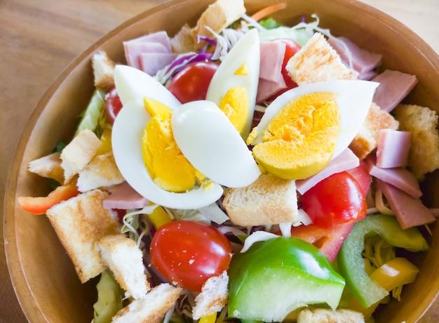 Nahaufnahme des frischen organischen salats mit schinken und gekochtem ei.