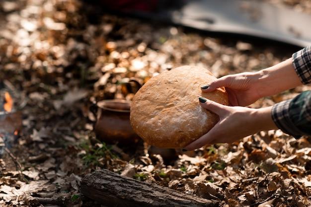 Nahaufnahme des frischen rustikalen brotes in der hand einer frau.